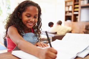 Smiling student doing homework at table.