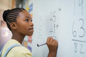 Girl doing addition problems at a whiteboard